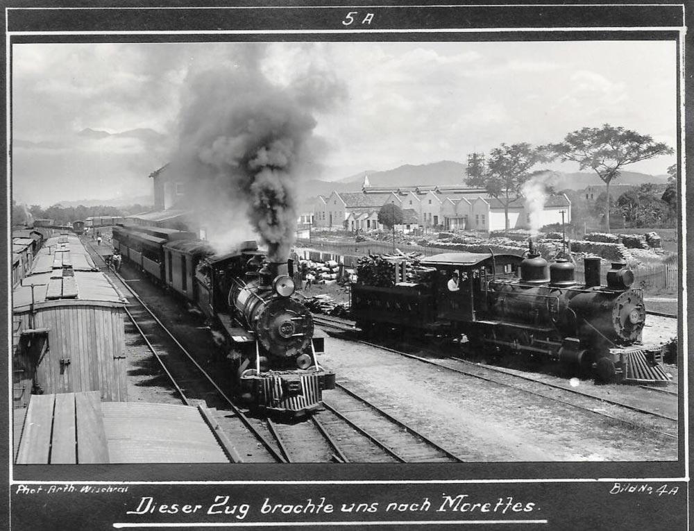 """""""Este trem nos trouxe a Morretes."""" Duas locomotivas a vapor em primeiro plano; à esquerda vagões feitos de madeira. No plano intermediário, a fábrica de papel mencionada no texto e visitada; ao fundo, a Serra do Mar. (Foto: Arthur Wischral/coleção Key Imaguire.)"""