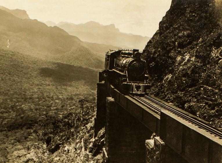 Locomotiva passando pelo Viaduto do Carvalho, ao fundo parte da Serra do Mar. (Foto: Arthur Wischral/Acervo Museu Paranaense)