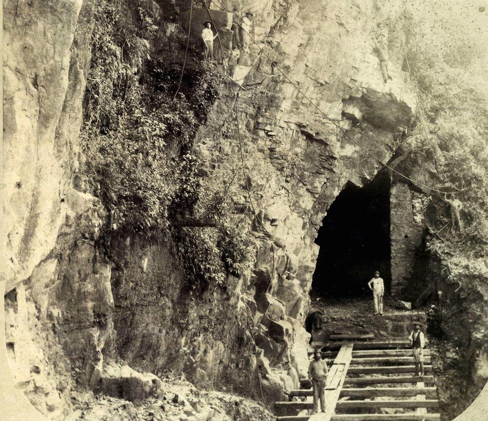Obras de escavação de túnel no Pico do Diabo, observe os trabalhadores na rocha da montanha. (detalhe de foto de Marc Ferrez/arquivo Biblioteca Nacional)