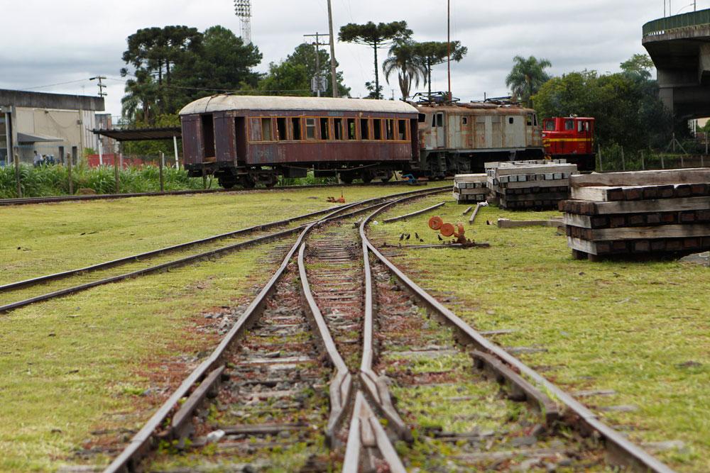 No pátio da ABPF-PR encontramos os elementos típicos de uma Ferrovia: trilhos, dormente e trens. Ao fundo vemos um carro de passageiros dos anos 1940, uma locomotiva diesel-elétrica da década de 1950 e uma pequena locomotiva diesel francesa também dos anos 1950. (Foto: Jonathan Campos/GP)