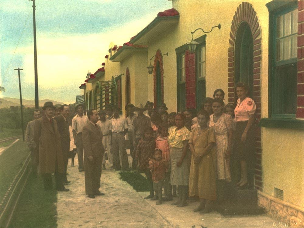 O superintendente da RVPSC, Durival Britto, entregando casas para os funcionários da linha Paranaguá-Curitiba nos anos 1940. A fotografia foi colorida manualmente após a revelação segundo costume da época. (Foto: Acervo do Instituto Histórico e Geográfico do Paraná)