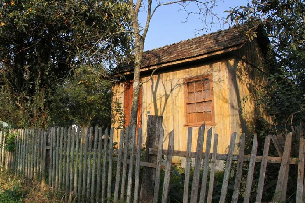 """Singela casa de madeira junto aos trilhos do bairro Cajuru em Curitiba. (Foto: livro """"Pelos Trilhos"""")"""