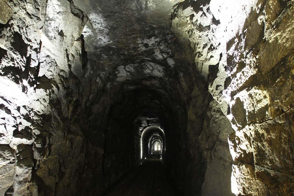 Parte do túnel sem revestimento, na rocha bruta da montanha. Um pequeno vagão elétrico leva o visitante até a entrada da cave. (Foto: Jonathan Campos/GP)