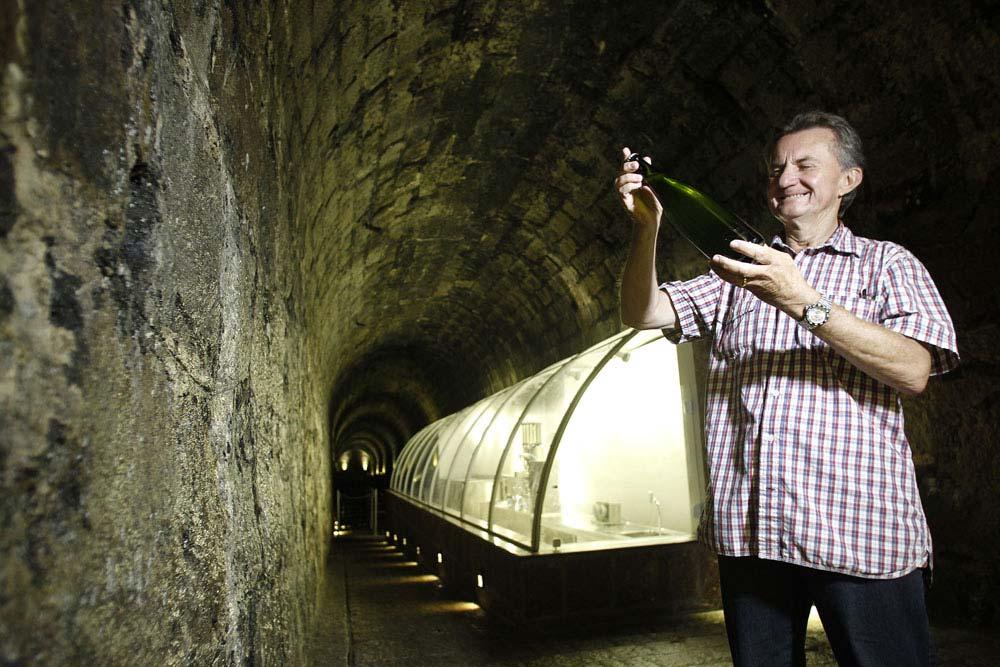 O empresário Ari Portugal com um garrafa de espumante. Ao fundo vemos o espaço onde as leveduras são eliminadas e o espumante já pronto recebe o lacre. (Foto: Jonathan Campos/GP)