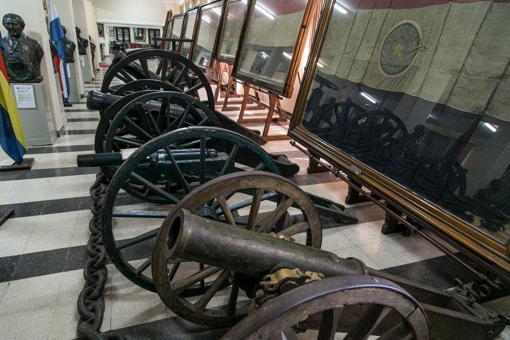 Imagem - Canhões que foram utilizados no conflito. Ao fundo bandeiras dos regimentos paraguaios, que foram devolvidas pelo argentino Perón em 1954