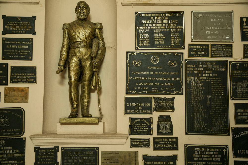 Imagem - Muitas placas relacionadas ao conflito e estátuas fazem parte da decoração do espaço. Na foto, a estátua de Solano López.